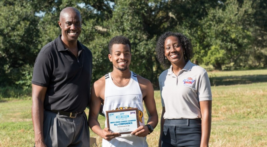 GCAC Cross Country Champion Kwame Jackson, with conference commissioner Steve Martin, left and GCAC President Kiki Baker Barn