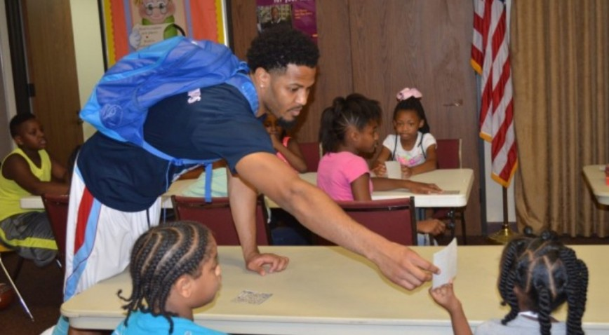 Jamarqus Jones, a guard/forward for Talladega's basketball team helps at kids at a Summer reading program in his hometown.